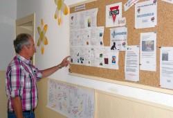 Helmut Oehler vor der Pinnwand mit vielen Angeboten des CVJM